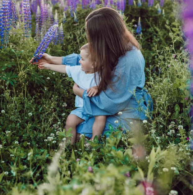 Woman in the chronic pain community holding a baby and picking flowers.