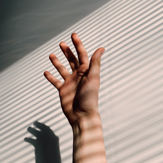 Hand stretches for chronic pain with shadow in background.