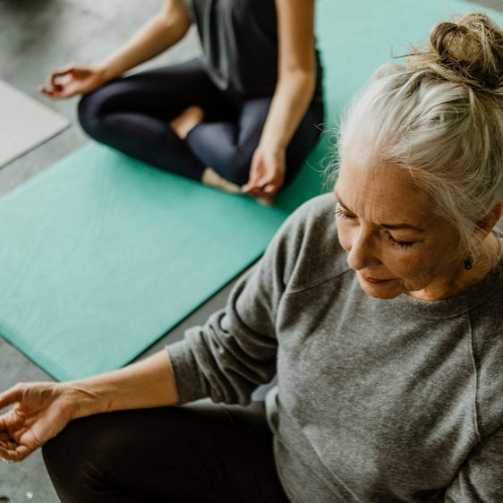 Woman in yoga pose using physical exercise for chronic pain.