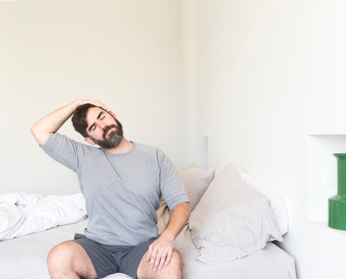Man stretching in bed due to chronic neck and back pain.